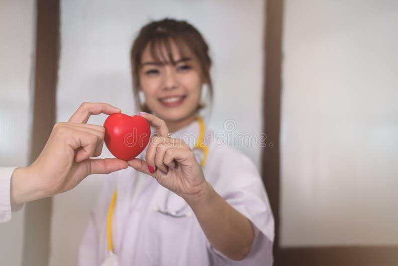 Doktor som rymmer röd hjärta på sjukhuset läkarundersökning sjukvård, cardi arkivfoto