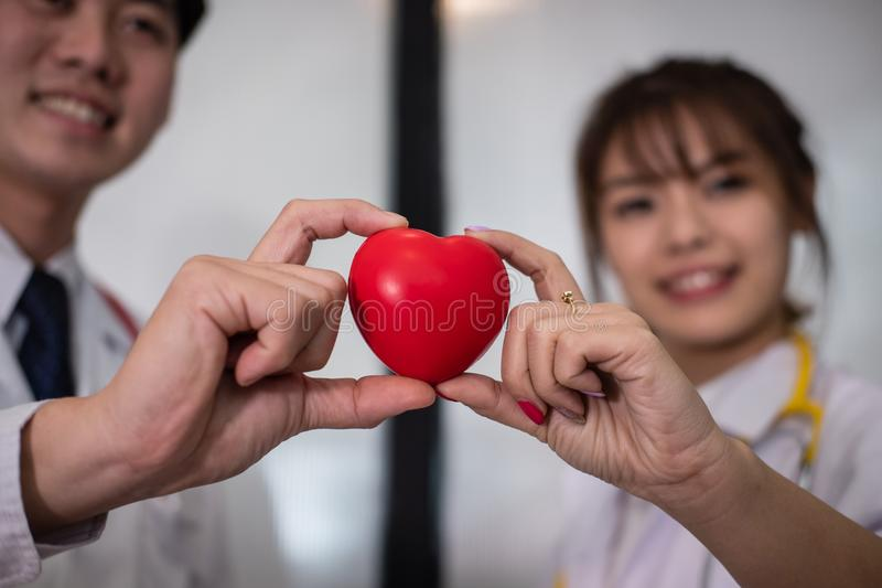 Doktor som rymmer röd hjärta på sjukhuset läkarundersökning sjukvård, cardi royaltyfri foto