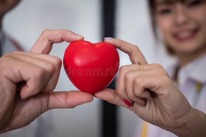 Doktor som rymmer röd hjärta på sjukhuset läkarundersökning sjukvård, cardi royaltyfria foton
