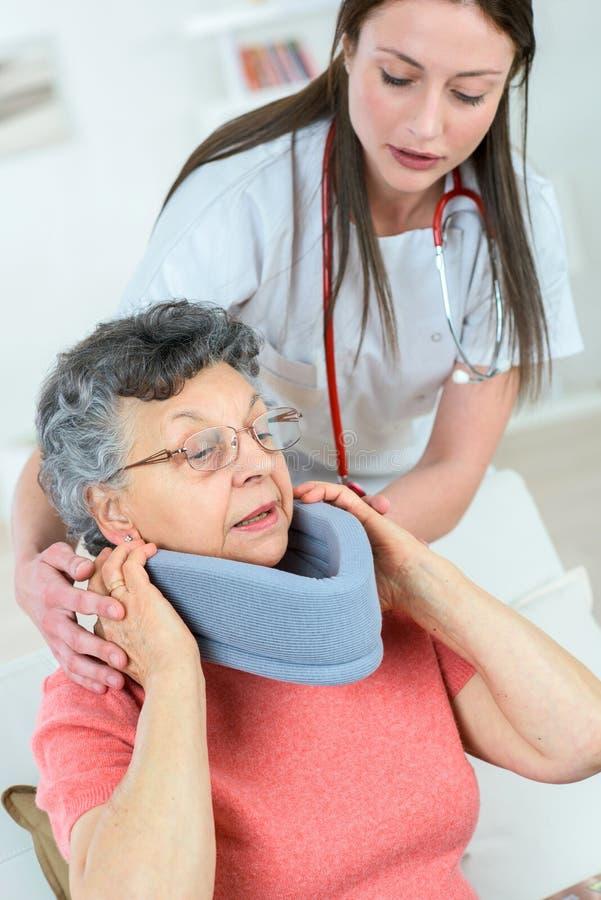 Doktor som sätter halsstaget på kvinna arkivbild