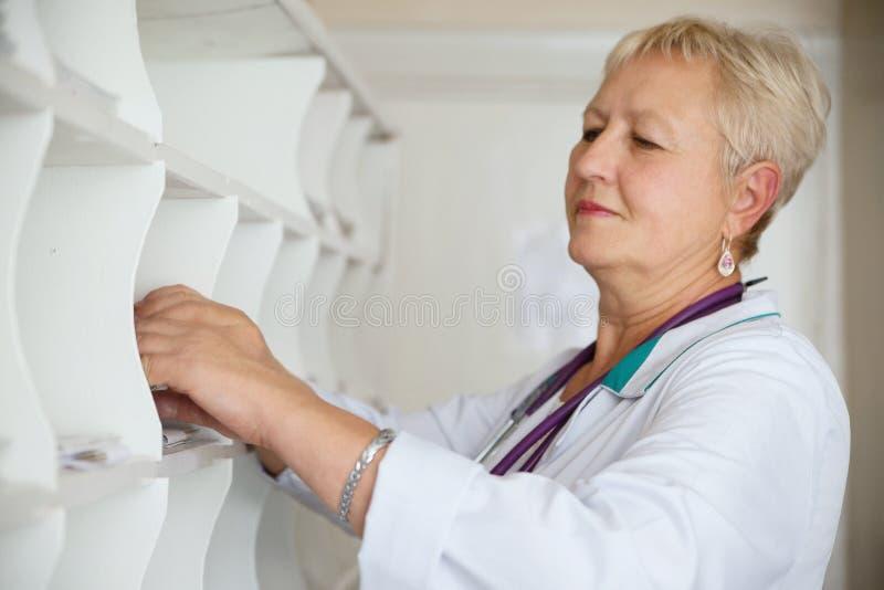 Doktor som söker det medicinska diagrammet i klinik royaltyfri fotografi