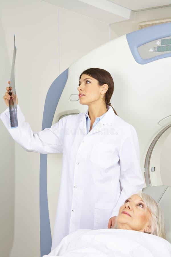 Doktor som ser röntgenstrålebild nära tålmodig arkivbild