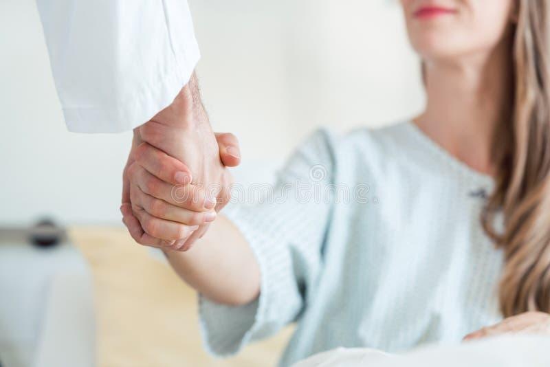 Doktor som skakar handen av patienten i sjukhussäng arkivfoton