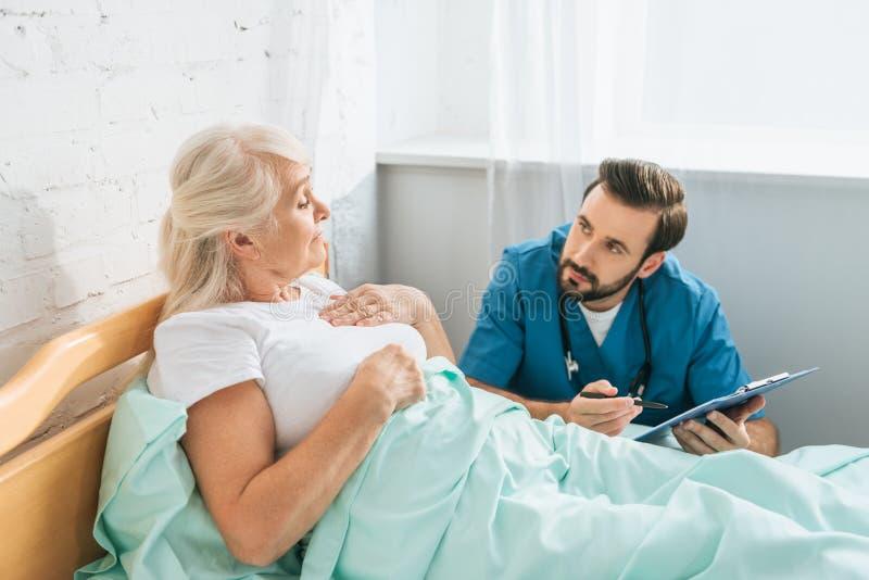 doktor som skriver på skrivplattan och ser den sjuka höga kvinnan royaltyfria foton
