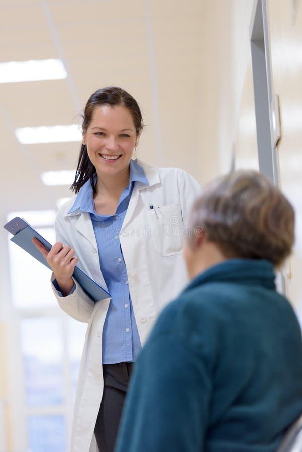 Doktor som smilling till den höga patienten royaltyfri bild