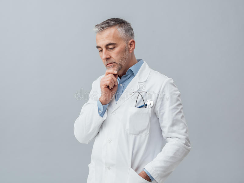 Doktor som tänker med handen på hakan royaltyfri fotografi