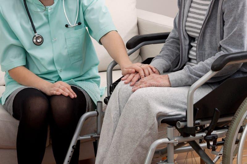 Doktor som talar med den åldriga patienten royaltyfria bilder