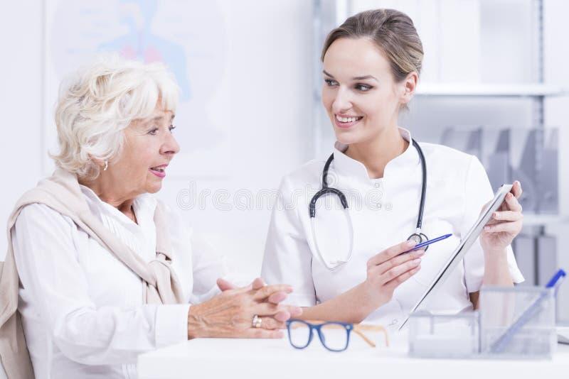 Doktor som talar med den höga kvinnan arkivfoton