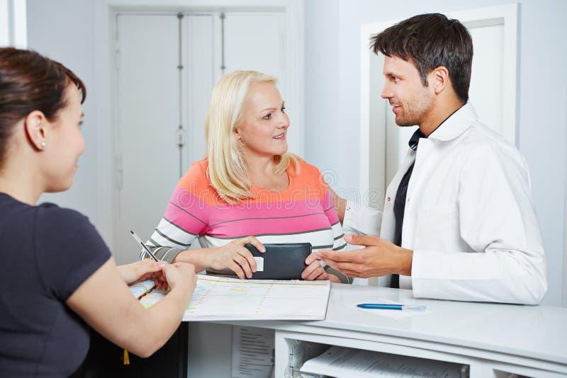 Doktor som talar med den höga kvinnan på mottagandet royaltyfri fotografi
