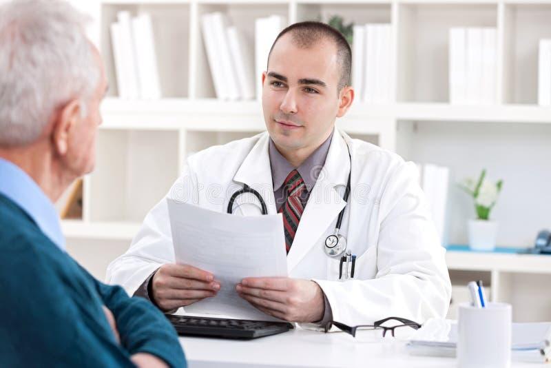 Doktor som talar med den höga tålmodign royaltyfria bilder