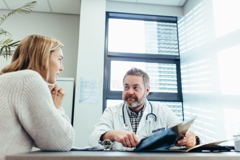Doktor som talar med den kvinnliga patienten under konsultation arkivfoton