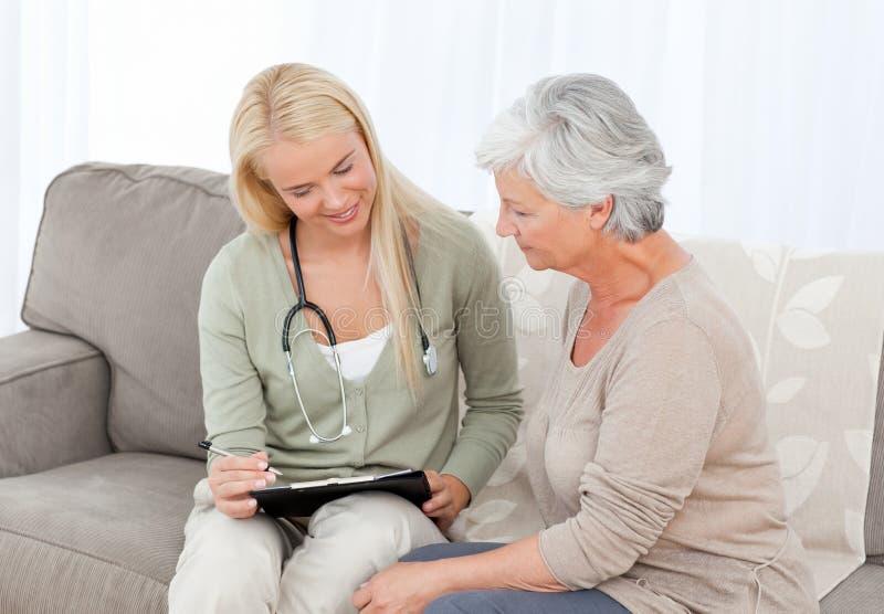 Doktor som talar med henne som är patient arkivfoton