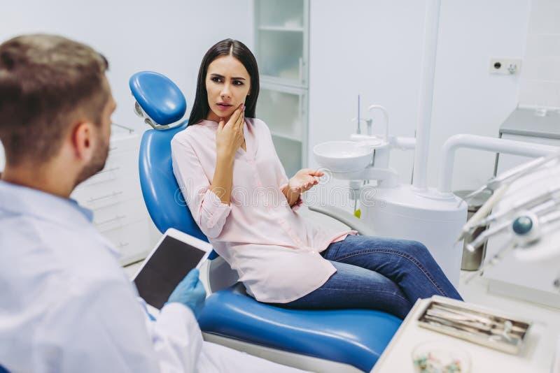 Doktor som talar med patienten som har tandvärk royaltyfria bilder