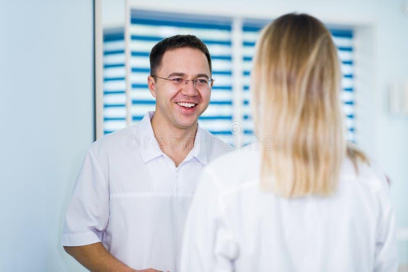 Doktor som talar och skrattar med hans sjuksköterskaassistent royaltyfria bilder