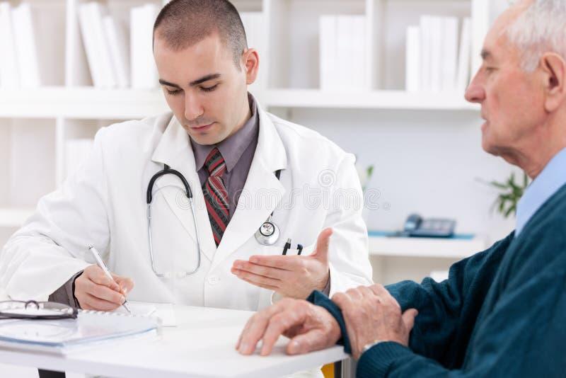 Doktor som talar till den höga patienten royaltyfria foton