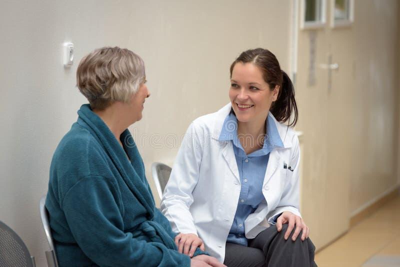 Doktor som talar till den höga patienten arkivfoton