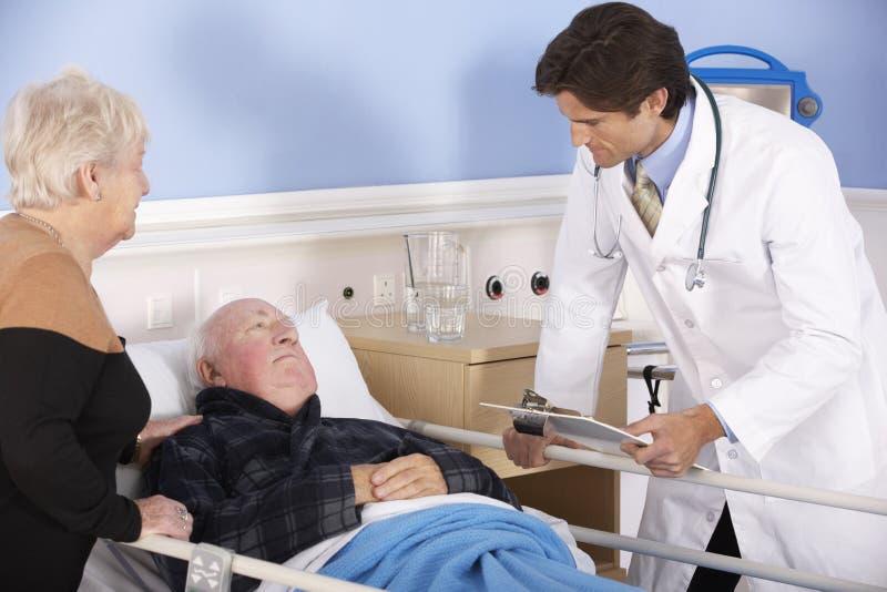 Doktor som talar till höga par i sjukhus arkivfoto