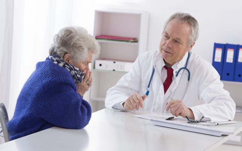 Doktor som talar till hans kvinnliga höga patient royaltyfri foto