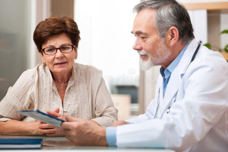 Doktor som talar till hans kvinnliga höga patient royaltyfria foton