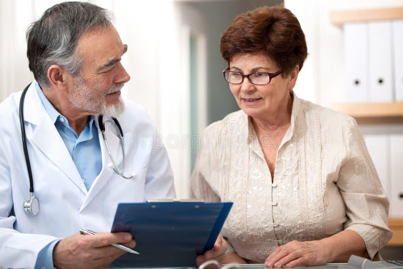 Doktor som talar till hans kvinnliga höga patient royaltyfri bild