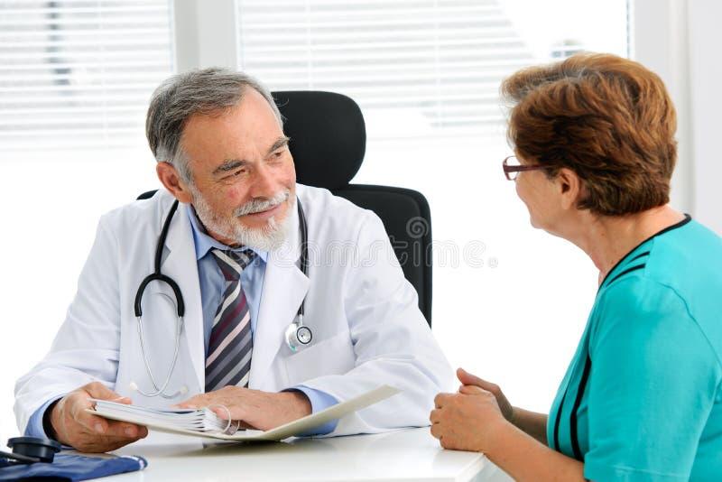 Doktor som talar till hans kvinnliga patient arkivbild