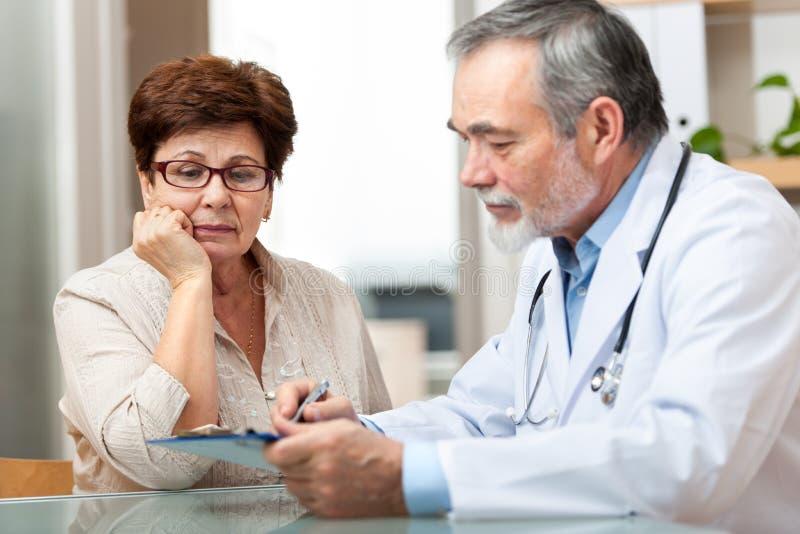 Doktor som talar till hans kvinnliga tålmodig royaltyfri bild