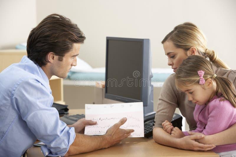 Doktor som talar till modern och barnet arkivbild