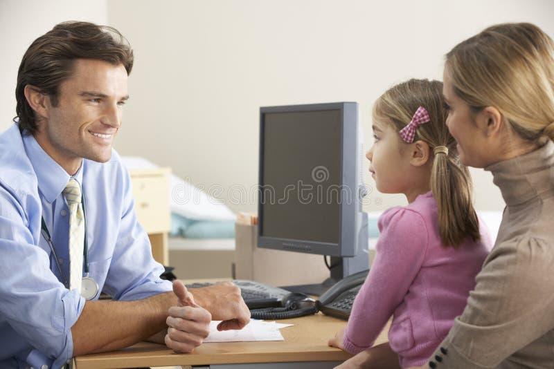 Doktor som talar till modern och barnet royaltyfria foton