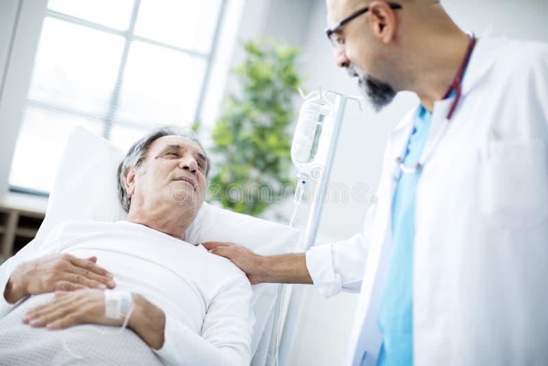 Doktor som talar till patienten i sjukhussäng royaltyfri bild