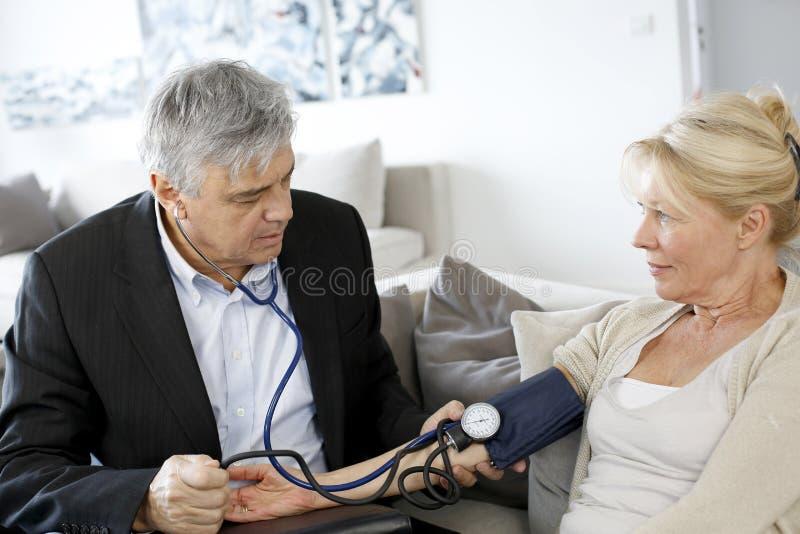 Doktor som tar blodtryck till den äldre kvinnan arkivbilder