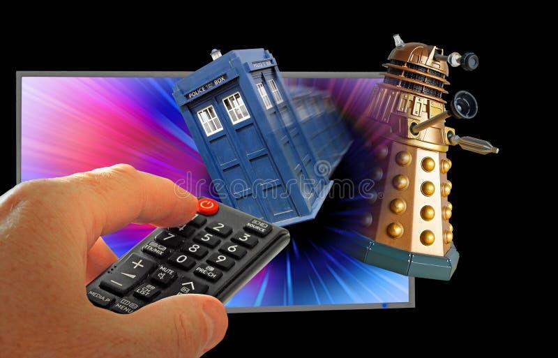 Doktor som tardis jagar dalek till och med handen för utrymmeTV-programfjärrkontroll arkivbilder