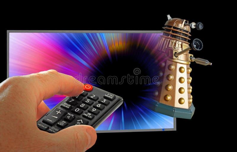 Doktor som tardis jagar dalek till och med handen för utrymmeTV-programfjärrkontroll royaltyfri fotografi