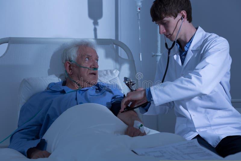 Doktor som undersöker den äldre patienten arkivbilder