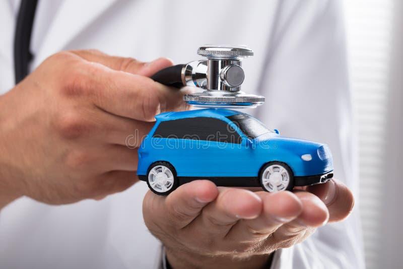 Doktor som undersöker den blåa bilen royaltyfria bilder