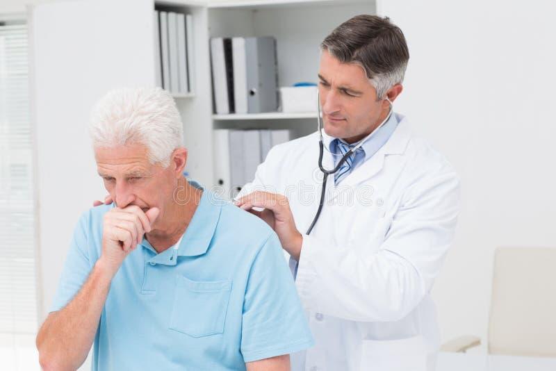 Doktor som undersöker den hostande höga patienten royaltyfri fotografi