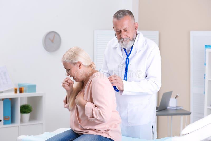 Doktor som undersöker den hostande mogna kvinnan arkivbild