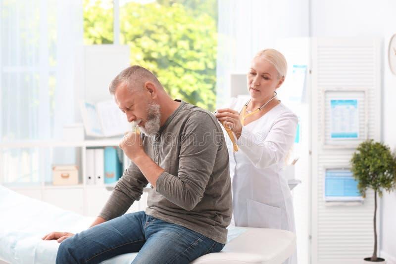 Doktor som undersöker den hostande mogna mannen arkivbild