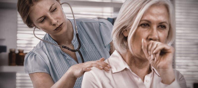 Doktor som undersöker den hostande patienten royaltyfri foto
