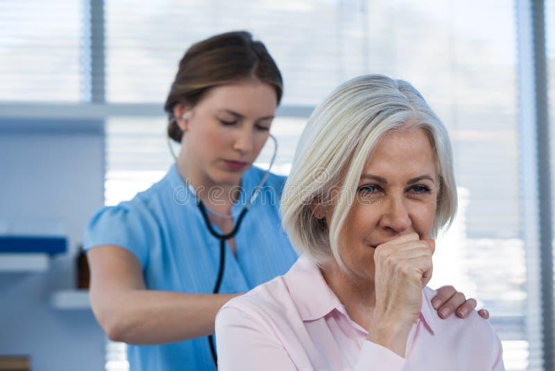 Doktor som undersöker den hostande patienten royaltyfria foton