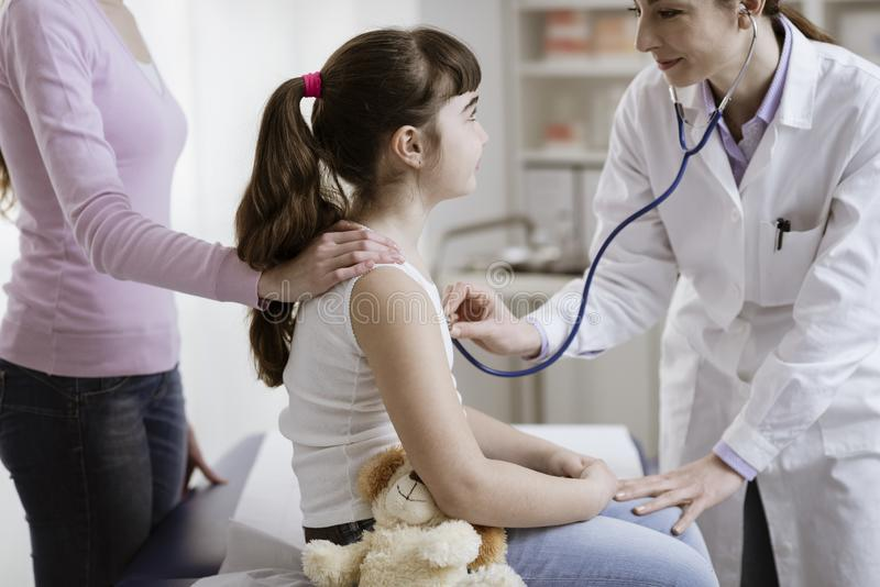 Doktor som undersöker en gullig le flicka med en stetoskop arkivfoto