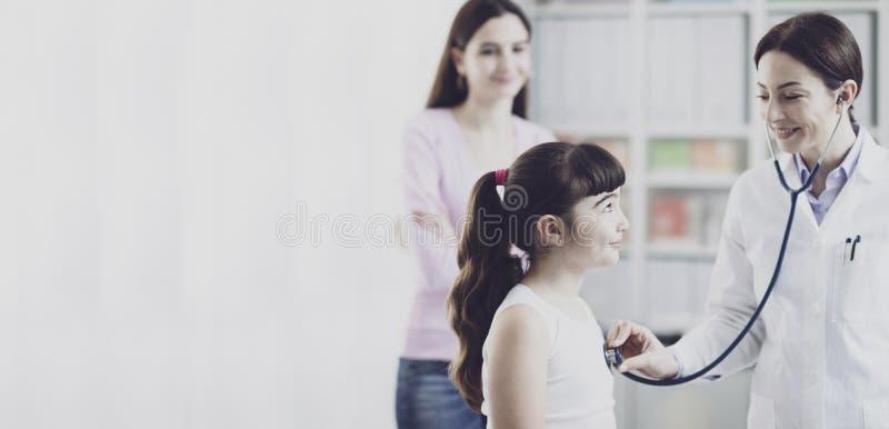 Doktor som undersöker en gullig le flicka med en stetoskop arkivbild