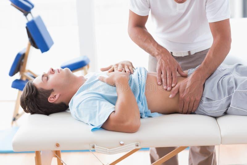 Doktor som undersöker hans tålmodiga mage fotografering för bildbyråer