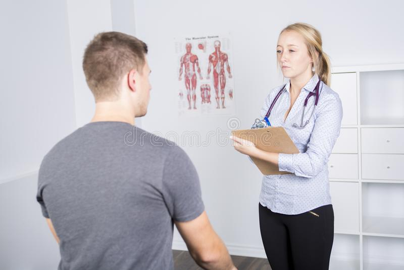 Doktor som undersöker hennes patient i medicinskt kontor royaltyfria bilder