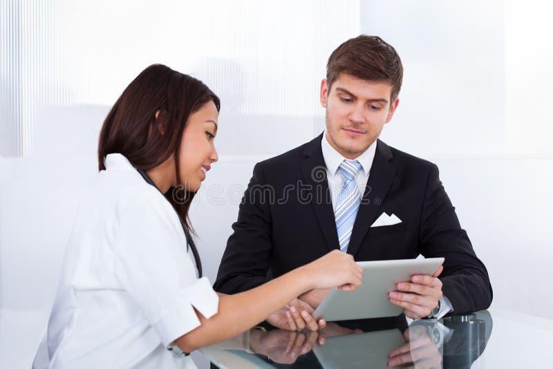Doktor som visar den digitala minnestavlan till affärsmannen royaltyfria foton