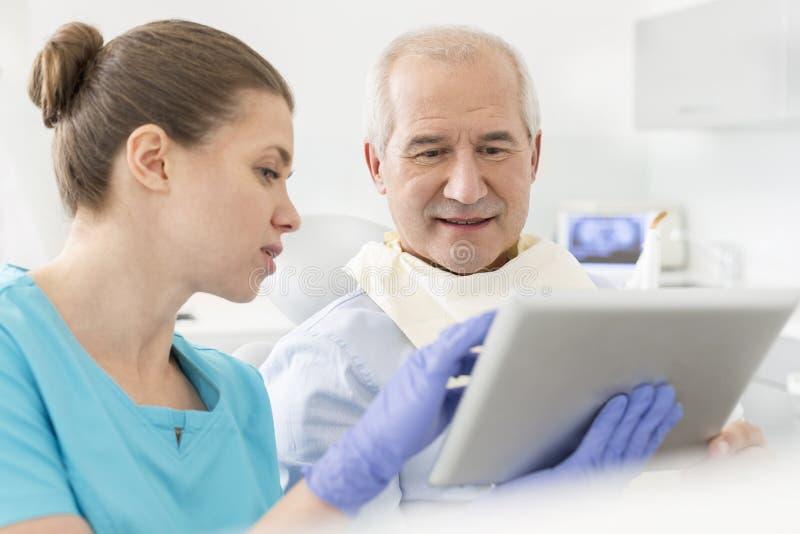 Doktor som visar den digitala minnestavlan till den höga patienten på den tand- kliniken royaltyfria bilder