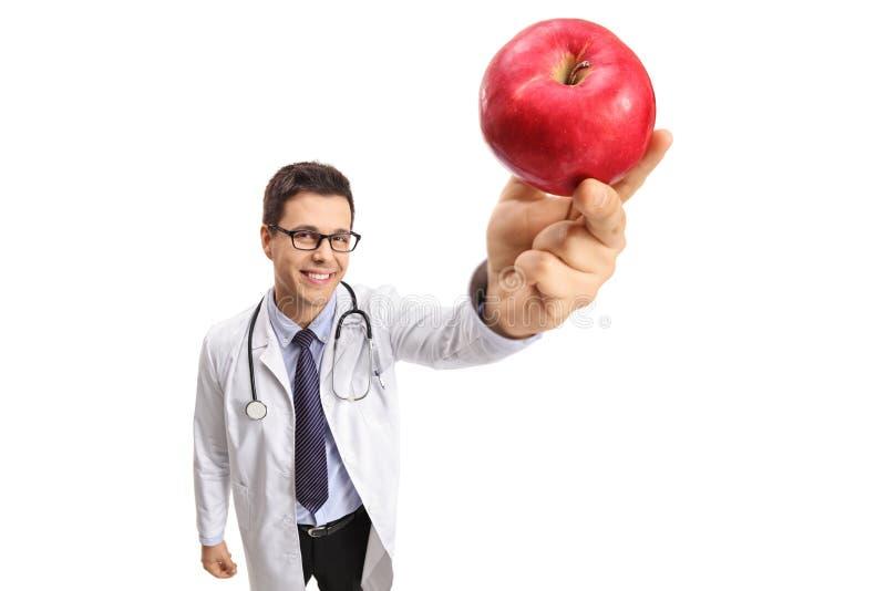 Doktor som visar ett äpple arkivbild