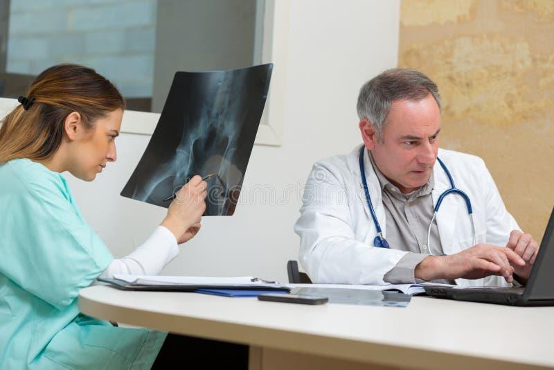 Doktor som visar röntgenstrålen till kollegan i medicinskt kontor royaltyfria foton