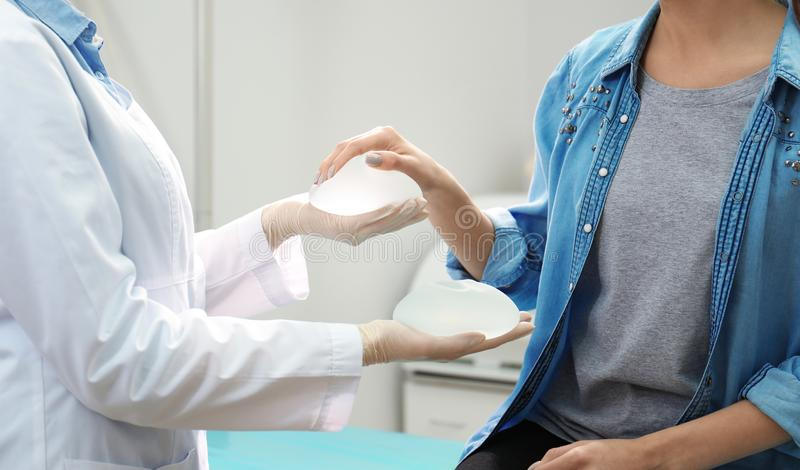 Doktor som visar silikonimplantat för bröststigande till patienten i kliniken, closeup royaltyfria foton