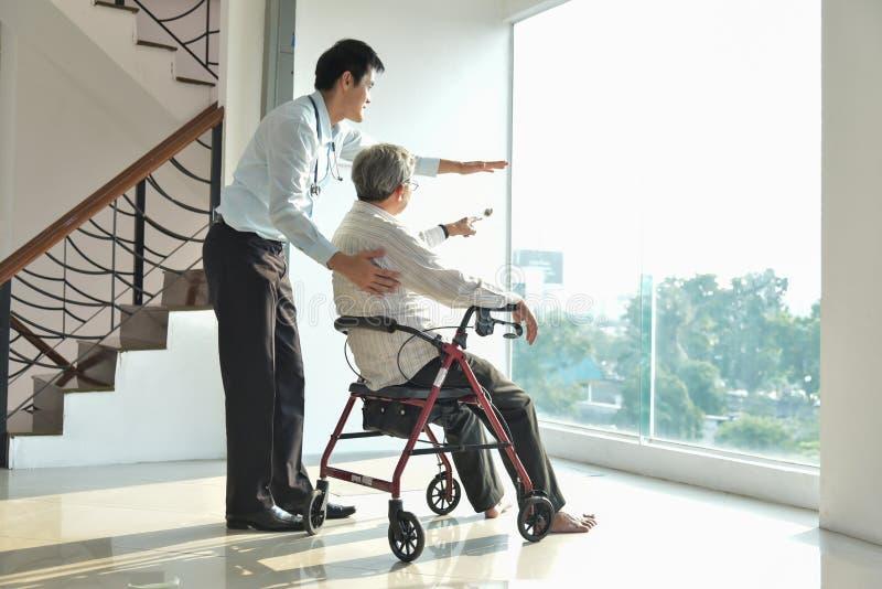 Doktor spricht mit seinem älteren männlichen Patienten in einem medizinischen Raum stockfoto