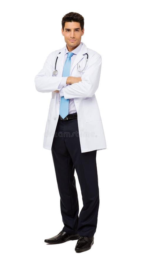 Doktor Standing Arms Crossed gegen weißen Hintergrund lizenzfreie stockbilder